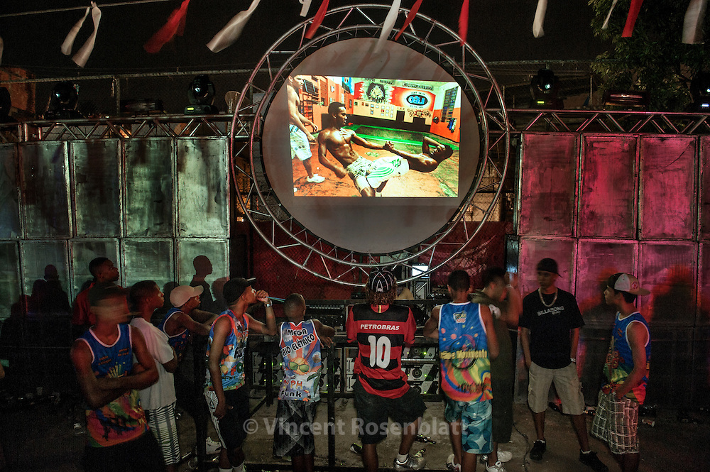 """Projection of the photographic series """"Rio Baile Funk"""" during a Baile, here in the favela Vila Cruzeiro, in a giant Baile Funk at the football """"Campo da Ordem""""; Complexo da Penha - northern area of Rio de Janeiro. After years documenting and photographing  the bailes funk, it seemed only fair to show this work where it actually took place.."""