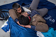 ATHENS, GREECE - FEBRUARY 05: A young Syrian boy comforts his father inside a ward in the Pireaus port where more than 300 hundred refugees are stranded after arriving during the night by ferry at the port from the Greek Islands on February 05, 2015 in Athens, Greece. A warehouse has been opened at the Pireaus port E1 gate to house essentials distributed by volunteers to the refugees stranded after arriving in Athens. Photo: © Omar Havana. All Rights Are Reserved
