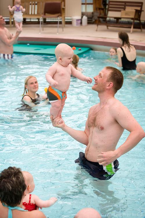Hafsteinn Halldórsson (35) with his son Dagur (6 months) at a babyswimming lesson in Mosfellsbær. Hafsteinn holding Dagur in one hand. Other parents watching them.