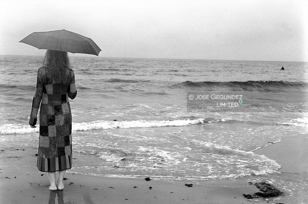 Mujer joven con paraguas en la orilla del mar...Young Woman Standing Under Cloudy Sky