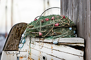 Close up photography of fishing net placed on part of an old wooden fishing boat, with blurred out background. No people. Scandinavia