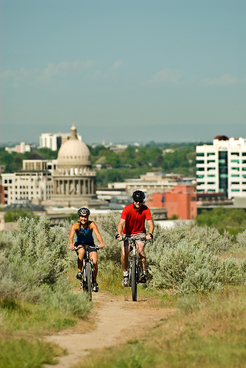 Idaho. Boise. Couple mountain biking in the foothills with the city skyline in the background. MR