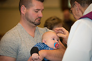 Jerrod Koenen holds his 4-month-old son Edison, as he receives ashes on his forehead from Deacon Pat Knier at SS. Peter and Paul Church in Kiel, Wis., on Ash Wednesday, March 1. (Sam Lucero | The Compass)
