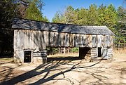 This old barn allows driving through the center in order to more easily transfer hay to the loft. Draft animals and milk cows were fed the hay in the stalls below during winter months. Cable Mill Historic Area, Cades Cove, Tennessee. Cades Cove, once home to numerous settlers, is an isolated valley located in Great Smoky Mountains National Park, USA. Today Cades Cove is the most popular destination for visitors to the park, attracting over two million visitors a year, due to its well preserved homesteads, scenic mountain views, and abundant display of wildlife.