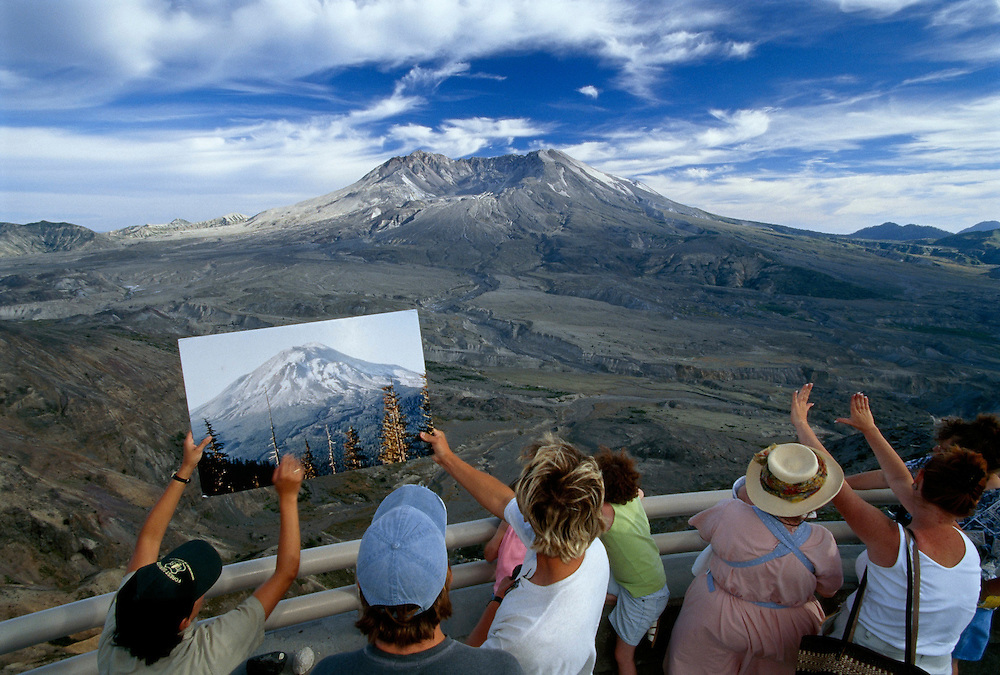 Visitors compare the cone of Mt. St. Helens with an earlier photo of it before the eruption.