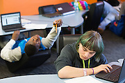 David Riggsbee hands an eraser to Brandon Healy, right, while they work in a Cyber Lounge at Integrated Arts & Technology High School in Rochester, New York on Tuesday, February 23, 2016. The district is in the early stages of a planned 1:1 device to student program.