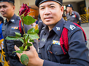 "14 FEBRUARY 2015 - BANGKOK, THAILAND: A Thai police officer holds a red rose handed out by a democracy protestor in Bangkok. Dozens of people gathered in front of the Bangkok Art and Culture Centre in Bangkok Saturday to hand out red roses and copies of George Orwell's ""1984."" Protestors said they didn't support either Red Shirts or Yellow Shirts but wanted a return of democracy in Thailand. The protest was the largest protest since June 2014, against the military government of General Prayuth Chan-Ocha, who staged the coup against the elected government. Police made several arrests Saturday afternoon but the protest was not violent.      PHOTO BY JACK KURTZ"