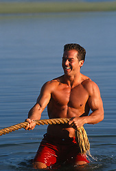 Good looking man pulling a rope in a lake