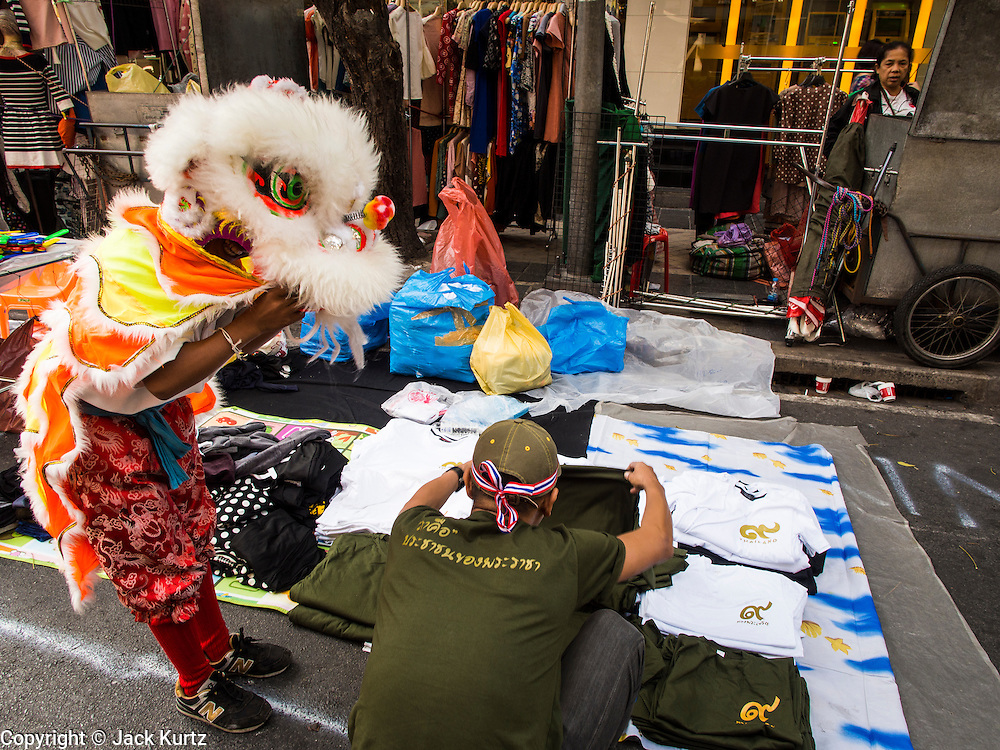17 JANUARY 2014 - BANGKOK, THAILAND: A Chinese Lion dancer gets money from a vendor at the Shutdown Bangkok Lumpini protest site in Bangkok. Friday was day 5 of the anti-government Shutdown Bangkok protests. The protest, led by the People's Democratic Reform Committee, is calling for the suspension of elections pending political reform in Thailand. There was violence at several sites in Bangkok Friday, including running battles between government opponents and supporters at one site and an IED attack by unknown assailants on anti-government protestors at another site.    PHOTO BY JACK KURTZ