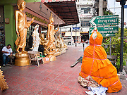 "05 JULY 2011 - BANGKOK, THAILAND:     A wrapped Buddha statue and other Buddha statues for sale on Bamrung Muang Street in Bangkok. Buddha statues are wrapped in saffron cloth before they moved, either from the factory or the store. Thanon Bamrung Muang (Thanon is Thai for Road or Street) is Bangkok's ""Street of Many Buddhas."" Like many ancient cities, Bangkok was once a city of artisan's neighborhoods and Bamrung Muang Road, near Bangkok's present day city hall, was once the street where all the country's Buddha statues were made. Now they made in factories on the edge of Bangkok, but Bamrung Muang Road is still where the statues are sold. Once an elephant trail, it was one of the first streets paved in Bangkok, it is the largest center of Buddhist supplies in Thailand. Not just statues but also monk's robes, candles, alms bowls, and pre-configured alms baskets are for sale along both sides of the street.      PHOTO BY JACK KURTZ"