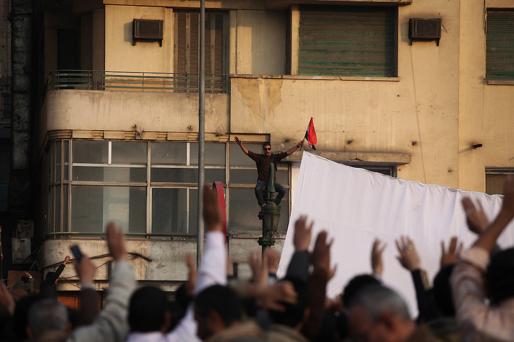A protester waves an Egyptian flag as crowds in Tahrir Square cheer below on 1 February 2011.