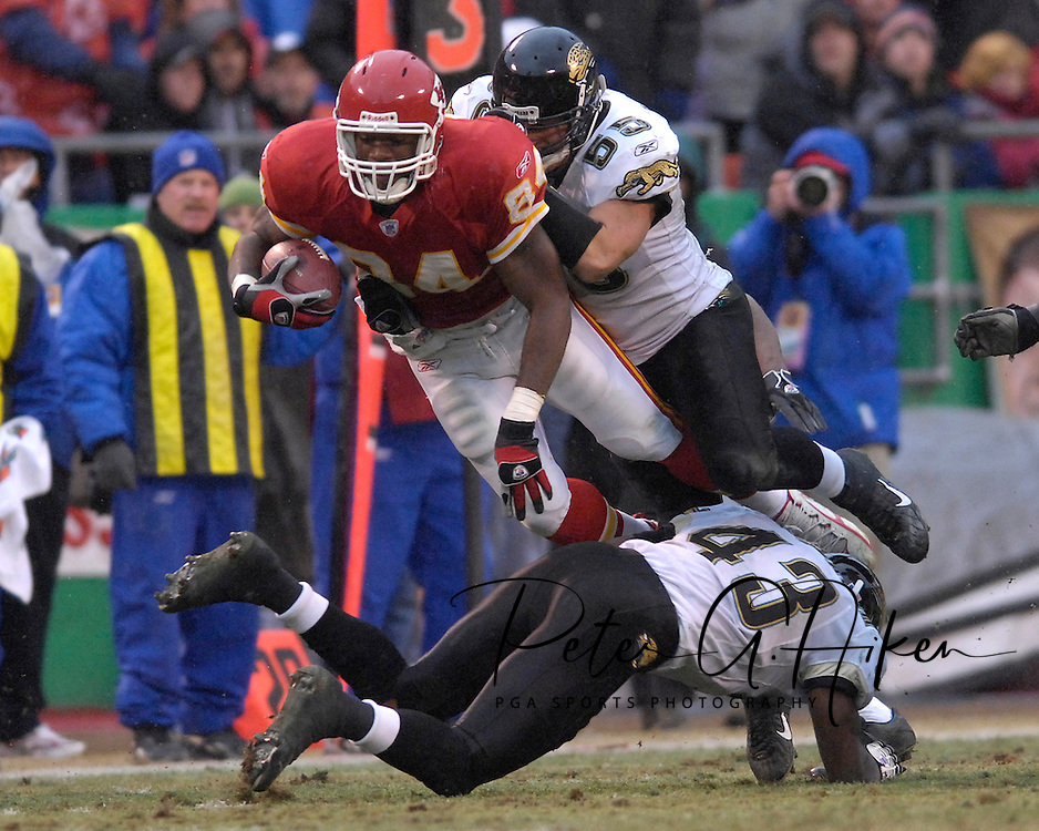 Kansas City Chiefs tight end Chris Wilson (84) is brought down by Jacksonville defenders Nick Greisen (55) and Gerald Sensabaugh (43) after picking up a first down in the fourth quarter at Arrowhead Stadium in Kansas City, Missouri, December 31, 2006.  The Chiefs beat the Jaguars 35-30.<br />