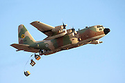 Israeli Air force C-130 Hercules 100 transport plane in flight drops cargo to the troups on the ground