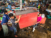 04 JANUARY 2016 - BANGKOK, THAILAND: Workers move an ice chest out of Bang Chak Market after the market closed permanently. The market closed January 4, 2016. The Bang Chak Market serves the community around Sois 91-97 on Sukhumvit Road in the Bangkok suburbs. About half of the market has been torn down. Bangkok city authorities put up notices in late November that the market would be closed by January 1, 2016 and redevelopment would start shortly after that. Market vendors said condominiums are being built on the land.       PHOTO BY JACK KURTZ