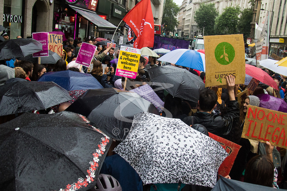 London, August 1st 2016. Protesters from Unite Hotel and Restaurant Workers Branch and other organisations demonstrate outside burger chain Byron's High Holborn outlet claiming that a recent training day was timed to coincide with a UK Border Agency raid, accusing the company of entrapment that has led to the deportation of 35 workers who it is alleged, using fake documentation had remained and were working in the UK illegally. PICTURED: Umbrellas cover the crowd as a light rain shower dampens the protest.