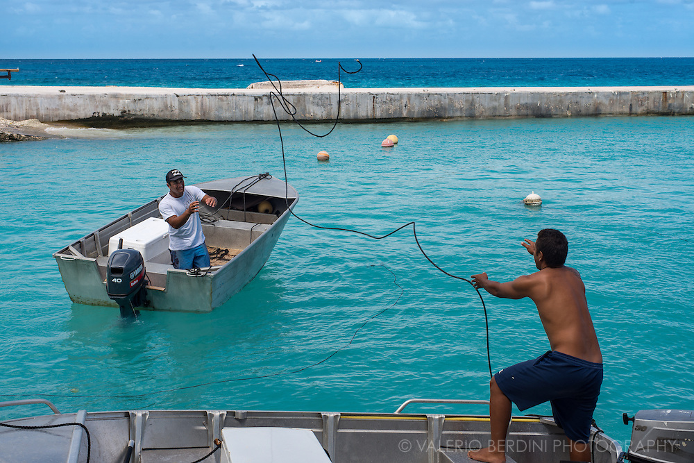two fishermen are getting ready to go out with the boat for a new fishing trip.