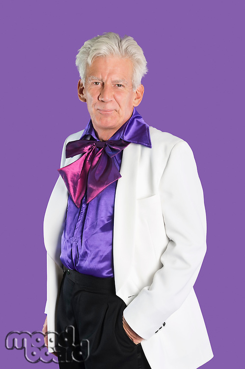 Portrait of senior man wearing old-fashioned suit against purple background