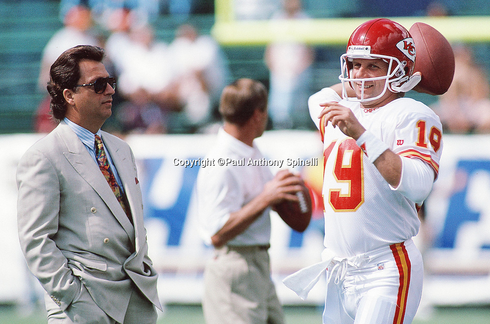 Kansas City Chiefs general manager Carl Peterson looks on while Kansas City Chiefs quarterback Joe Montana (16) smiles and throws a pass while warming up before the NFL football game against the San Diego Chargers on Oct. 17, 1993 in San Diego. The Chiefs won the game 17-14. (©Paul Anthony Spinelli)