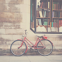 a red bicycle leans against a wall on a street in Cambridge, England beneath a vintage book store.