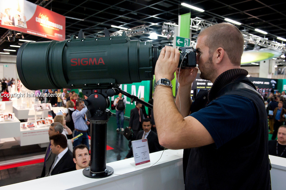 Visitor looking through very large telephoto lens by Sigma at Photokina digital imaging trade show in Cologne Germany 2010