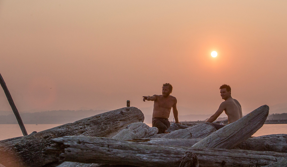 Craig Vienneau,right, and a friend take in the sunset at Holland Point Park below the Dallas Road Waterfront Trail in Victoria, British Columbia Canada on August 3, 2017. <br /> <br /> Smoke from wildfires in British Columbia&rsquo;s interior has drifted over Victoria and the lower mainland pushing air quality to a high risk level.