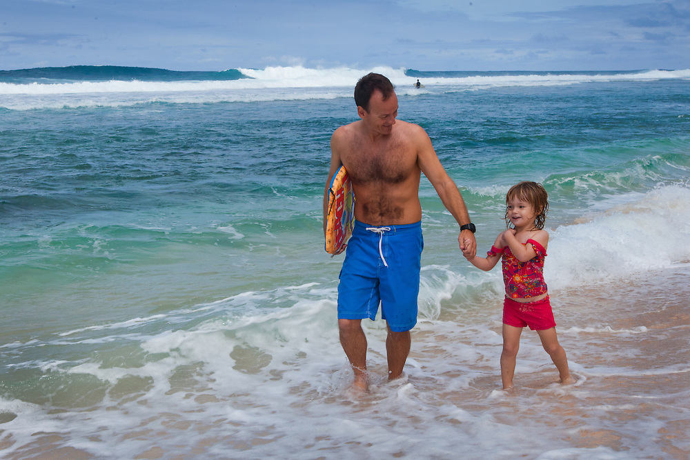 A father and his small daughter walk in the whitewater on the beach on Oahu's north shore in Hawaii
