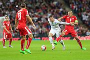England's Wayne Rooney fends off Switzerland's Gokhan Inler during the UEFA European 2016 Qualifying match between England and Switzerland at Wembley Stadium, London, England on 8 September 2015. Photo by Shane Healey.