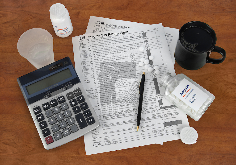 US Income Tax return form, calculator, aspirin, coffee cup, pencil and antidepressants on a wooden desk