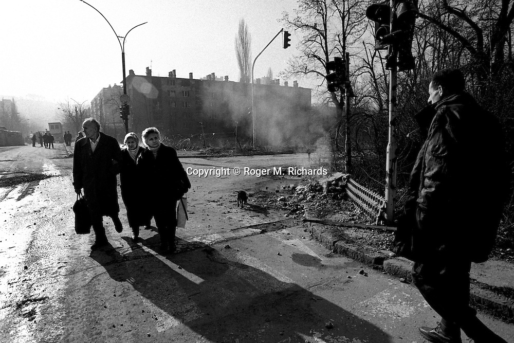 A Bosnian Serb militia man watches as people leave Grbavica and cross the Bratstvo i Jedinstvo Most (Brotherhood and Unity bridge) and enter Sarajevo during the final days of the siege of the city, Sarajevo, Bosnia and Herzegovina, February 1996. PHOTO BY ROGER RICHARDS