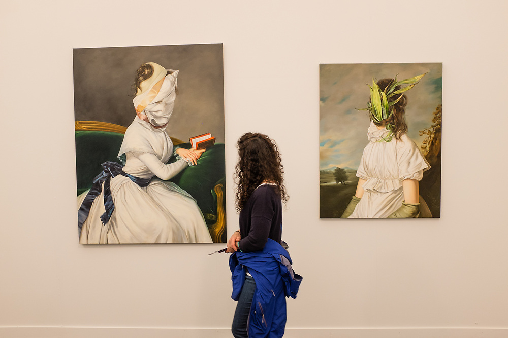 New York, NY - May 3, 2019. A woman with two surreal portrait paintings after old maters by Ewa Juszkiewicz in the lokal_30 Gallery booth at the Frieze Art Fair on New York City's Randalls Island.