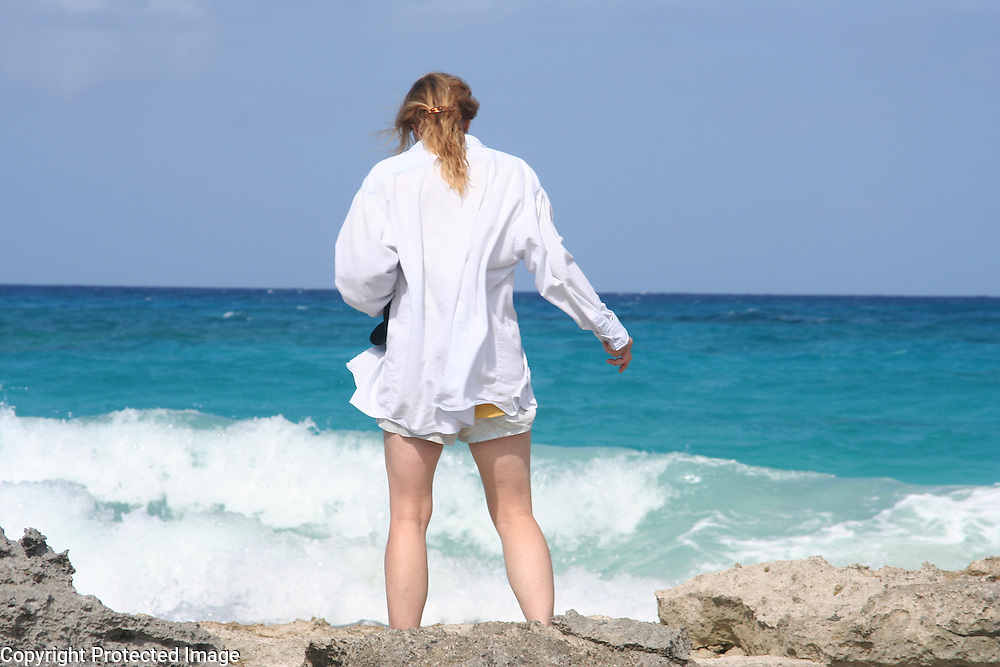 A woman stands before the surf on Stocking Island near George Town in the Great Exuma Islands of the Bahamas