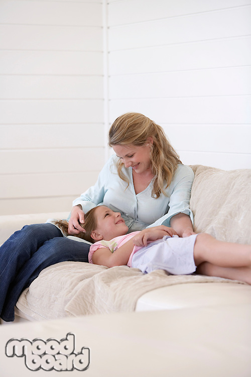 Daughter lying on mothers lap on couch