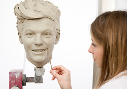 """© Licensed to London News Pictures. 19/02/2013. London, UK Sculptor Georgina Power works on the clay head of Louis Tomlinson. Madame Tussauds today released pictures of sculptors working on the life-like clay heads of the five members of pop band """"One Direction ' The clay heads will be used to create the moulds for their new wax figures. Niall, Liam, Louis, Harry and Zayn have been closely involved in the creation process giving the creative team two sittings at which hundreds of measurements were taken to ensure total accuracy. The clay heads will now be used to make the moulds for the final wax figures, which will be revealed in London. Photo credit : Madame Tussauds /LNP"""