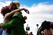 Two figures embrace in the crowd of the festival, Boomtown, Matterley Estate, Alresford Road, near Winchester, Hampshire, UK, August, 2010