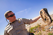 "03 MAY 2012 - VEKOL VALLEY, RURAL PINAL COUNTY, AZ:  Jon Young (CQ Jon), the BLM  Chief Ranger for Arizona, holds up a pair of slipper like foot coverings he found on Bureau of Land Management land south of Interstate 8 and west of Casa Grande in rural Pinal County. The area has been a hotbed of illegal immigrant and drug smuggling for years. The BLM has undertaken a series of ""surges"" in the area, increasing their law enforcement patrols and partnering with Border Patrol and Pinal County Sheriff's Department officers to reduce criminal activity in the area. Drug smugglers use to obscure the slippers to obscure their tracks as they walk through the desert.         PHOTO BY JACK KURTZ"