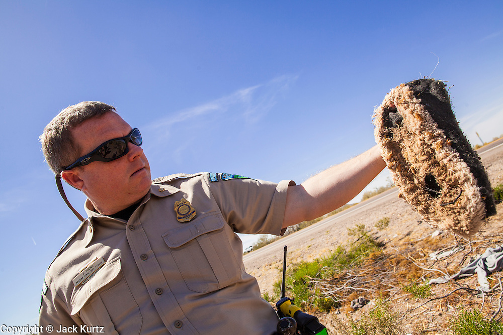 """03 MAY 2012 - VEKOL VALLEY, RURAL PINAL COUNTY, AZ:  Jon Young (CQ Jon), the BLM  Chief Ranger for Arizona, holds up a pair of slipper like foot coverings he found on Bureau of Land Management land south of Interstate 8 and west of Casa Grande in rural Pinal County. The area has been a hotbed of illegal immigrant and drug smuggling for years. The BLM has undertaken a series of """"surges"""" in the area, increasing their law enforcement patrols and partnering with Border Patrol and Pinal County Sheriff's Department officers to reduce criminal activity in the area. Drug smugglers use to obscure the slippers to obscure their tracks as they walk through the desert.         PHOTO BY JACK KURTZ"""