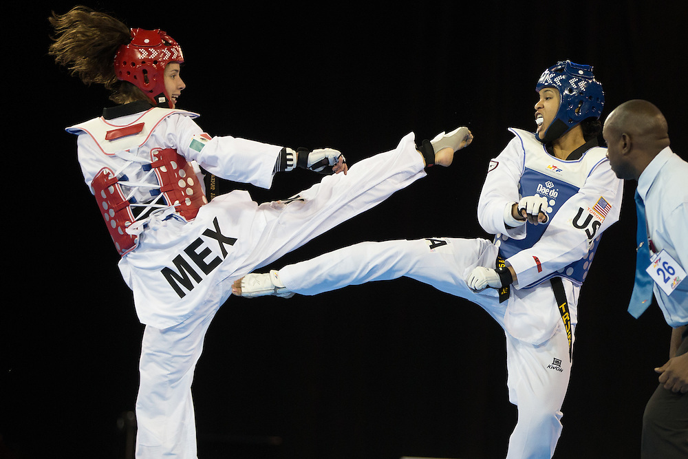 Victoria Heredia (L) of Mexico and Paige McPherson of the United States trade kicks in their gold medal contest in women's taekwondo -67 kg division at the 2015 Pan American Games in Toronto, Canada, July 21,  2015.  AFP PHOTO/GEOFF ROBINS