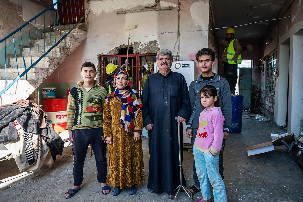 4 February 2019 – Mosul – Iraq – Entesar and Ismael stand for a photo with their children inside their family home in the al-Islah al Zirahee neighbourhood of West Mosul. <br /> <br /> Work is currently underway to rehabilitate their home with the support of UNDP's Funding Facility for Stabilization (FFS), which is supporting the rehabilitation of ten thousand homes across West Mosul, helping displaced families return home. <br /> <br /> © UNDP Iraq / Claire Thomas