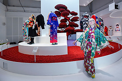 "© Licensed to London News Pictures. 26/02/2020. LONDON, UK. Visitor Sheila Cliffe, an author and Japanophile who lives in Tokyo, poses wearing her own kimono next to works on display. Preview of ""Kimono: Kyoto to Catwalk"", an exhibition celebrating the Japanese kimono.  Artworks are on show at yje V&A museum in South Kensington 29 February to 21 June 2020.  photo credit: Stephen Chung/LNP"