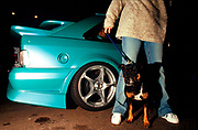 A girl stood next to a car, with her dog, Girlracers, Southend, UK 2004