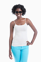 Happy young African American woman wearing sunglasses standing over white background