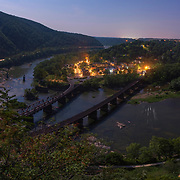 "The historic town of Harpers Ferry is illuminated from a full moon above; as seen from the edge of Maryland Heights.<br /> <br /> On the night of October 16th, 1859 a party of 17 armed men led by the militant abolitionist John Brown crossed the Potomac River over the B&O railroad bridge (the piers of which can be seen below at left) to seize the federal arsenal at Harpers Ferry and its stockpile of 100,000 rifles and muskets. With these weapons, Brown intended to facilitate an armed slave uprising that would spread throughout the entire South. <br /> <br /> While his raid failed, the news of John Brown's attempt was an earthquake that reverberated throughout the entire Union and split the fault line between North and South. denounced as a psychotic terrorist by Southerners, Brown was embraced by many Northern abolitionists as a martyr. This outpouring of support for Brown exasperated Southern suspicions of a yankee-abolitionist plot to subjugate the South under Northern control through emancipation; by force if necessary. Southern states, long fearful of slave revolts, revived the militia system to combat all future ""John Browns"" laying the foundation for what would become the Confederate Army. <br /> <br /> On the morning of his execution, John Brown handed a note to one of his guards that would become prophetic: ""I, John Brown, am now quite certain that the crimes of this guilty land will never be purged away but with blood..."" 16 months later, Confederate batteries in Charleston would open fire on Fort Sumter, and the bloody purge would begin."