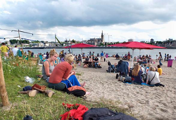 Nederland, Nijmegen, 19-07-2012 Aan de overkant van de rivier de Waal bij Nijmegen vermaken zich mensen aan de Waalstrand, wat tijdens de 4 daagse en zomerfeesten Habana heet. Dit mooie Waalstrandje is tijdens de Zomerfeesten een toevluchtsoord voor iedereen die rustig wil genieten van de zon en de rust, maar vooral ook van theater, pop, jazz en dans. Foto: Flip Franssen/Hollandse Hoogte