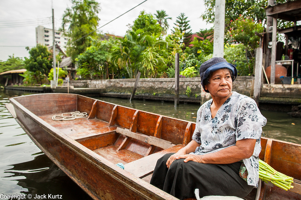 "17 NOVEMBER 2012 - BANGKOK, THAILAND:  A woman on a ""long tailed"" boat in Bangkok. Long tailed boats use big V8 car engines and have 30-40 foot long propeller shafts that extend past the back of the boat. Bangkok used to be known as the ""Venice of the East"" because of the number of waterways the criss crossed the city. Now most of the waterways have been filled in but boats and ships still play an important role in daily life in Bangkok. Thousands of people commute to work daily on the Chao Phraya Express Boats and fast boats that ply Khlong Saen Saeb or use boats to get around on the canals on the Thonburi side of the river. Boats are used to haul commodities through the city to deep water ports for export.    PHOTO BY JACK KURTZ"