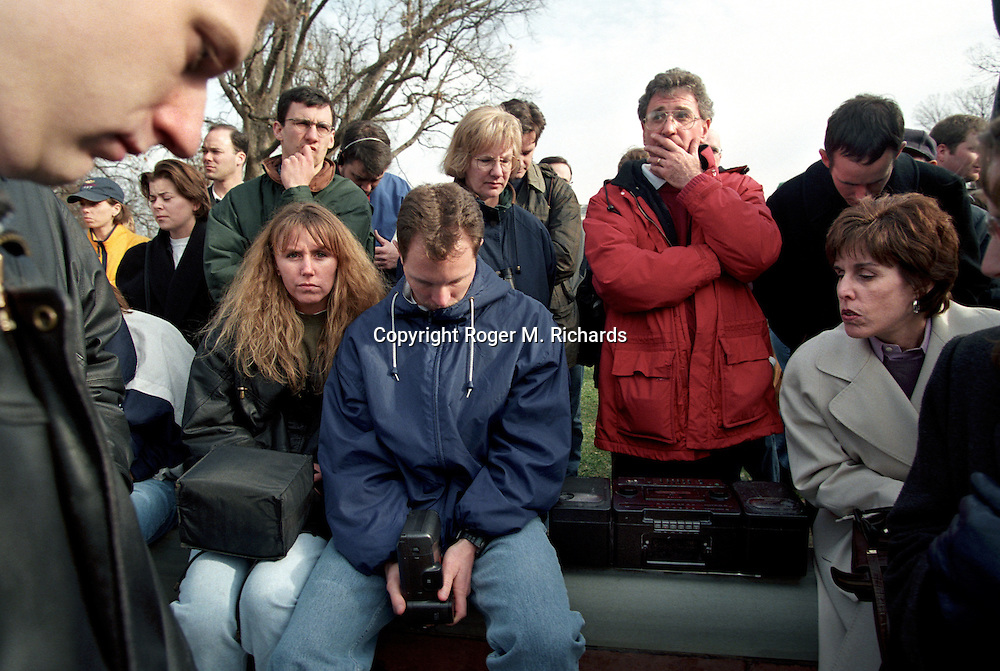 People listen to a radio outside the U.S. Capitol building as President Bill Clinton is impeached by the majority Republican U.S. House of Representatives, Washington, DC, December 19, 1998.  (Photo by Roger M. Richards)