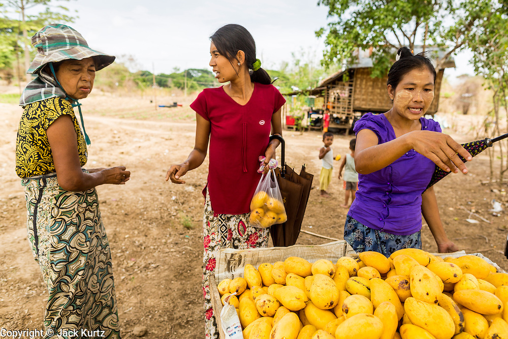 25 MAY 2013 - MAE SOT, TAK, THAILAND:     Burmese women haggle over the price of a fruit with a Burmese merchant (not in picture) who came out to their unofficial village of Burmese refugees north of Mae Sot, Thailand. They live on a narrow strip of land about 200 meters deep and 400 meters long that juts into Thailand. The land is technically Burma but it is on the Thai side of the Moei River, which marks most of the border in this part of Thailand. The refugees, a mix of Buddhists and Christians, settled on the land years ago to avoid strife in Myanmar (Burma). For all practical purposes they live in Thailand. They shop in Thai markets and see their produce to Thai buyers. About 200 people live in thatched huts spread throughout the community. They're close enough to Mae Sot that some can work in town and Burmese merchants from Mae Sot come out to their village to do business with them.   PHOTO BY JACK KURTZ