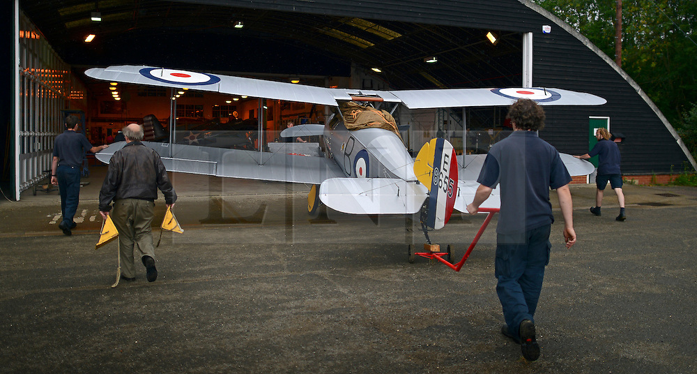 © Licensed to London News Pictures. 29/08/2012. Old Warden, UK. Workers move the Sopwith Snipe E6655, a reconstruction, into a hanger.  The Royal Airforce Museum unveils three World War One aircraft at the Shuttleworth Aerodrome in Bedfordshire today, 29th August 2012.  The Snipe, Albatros DVa and RE8 will fly in airshows before going on public display at the Museum's London site Photo credit : Stephen Simpson/LNP