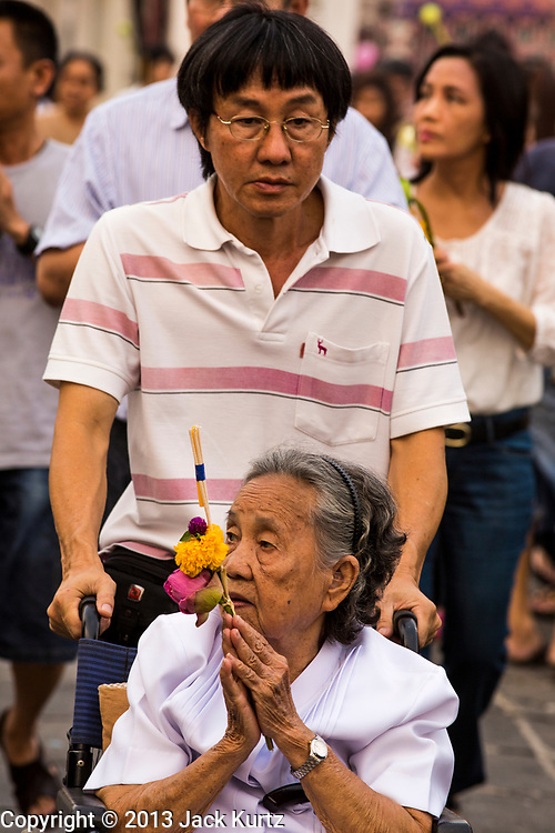 "25 FEBRUARY 2013 - BANGKOK, THAILAND: Thai woman in a wheelchair bows her head as she enters Wat Benchamabophit Dusitvanaram (popularly known as either Wat Bencha or the Marble Temple) on Makha Bucha Day. Makha Bucha is a Buddhist holiday celebrated in Myanmar (Burma), Thailand, Cambodia and Laos on the full moon day of the third lunar month (February 25 in 2013). The third lunar month is known in Thai is Makha. Bucha is a Thai word meaning ""to venerate"" or ""to honor"". Makha Bucha Day is for the veneration of Buddha and his teachings on the full moon day of the third lunar month. Makha Bucha Day marks the day that 1,250 Arahata spontaneously came to see the Buddha. The Buddha in turn laid down the principles his teachings. In Thailand, this teaching has been dubbed the 'Heart of Buddhism'.      PHOTO BY JACK KURTZ"