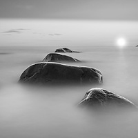 Beautiful sunset rendered in black and white. Stillness of the rocks blended with the timelessness of the waves.