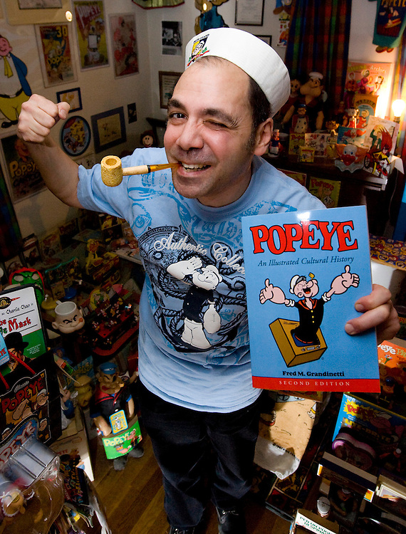 (Watertown, MA - 011709) - Local Boston Popeye expert Fred Grandinetti gives his best impression, complete with a corn cob pipe, as he talks about the character on its 80th birthday. He's standing in a room in his house filled with his personal Popeye collectables.